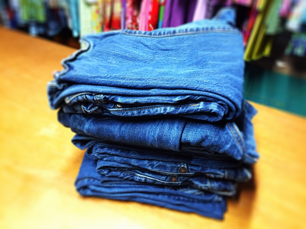a photograph of a stack of used blue jeans